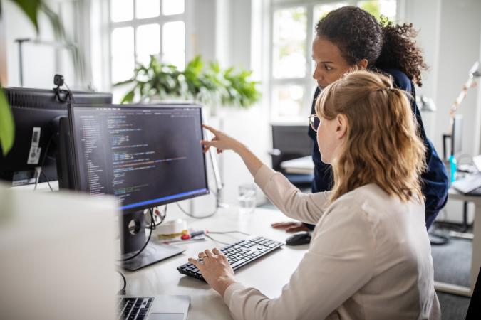 Two women coworkers working with computer programming