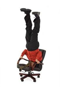Office worker doing headstand in chair