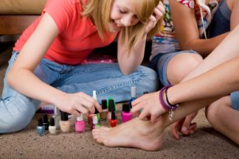 Girls painting toenails at a spa-theme birthday party