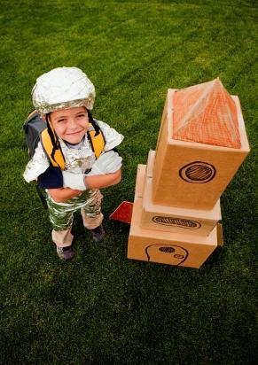 Kid astronaut with cardboard rocket ship