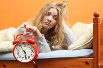 Unhappy woman waking up with alarm clock