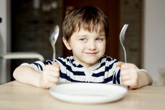 Happy little boy waiting for dinner