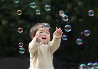 Girl Chasing Colorful Bubbles