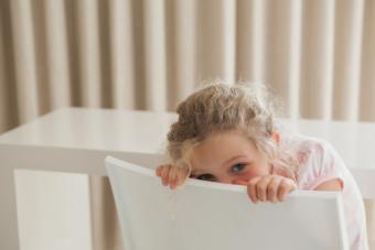 Girl hiding behind chair