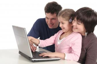 Parents and daughter using laptop