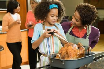 Mother and daughter basting a Thanksgiving turkey