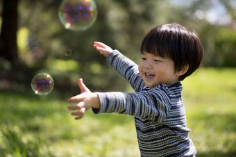 Asian toddler catching soap bubbles
