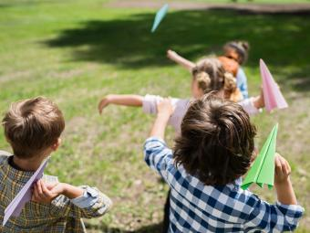 Young children throwing paper planes outdoors