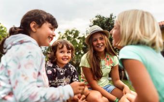 Four girls talking and telling jokes