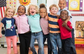 Kindergarten students hugging in classroom