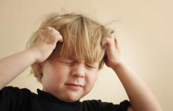 Boy scratching his head