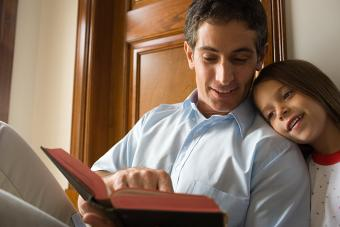 Father reading bible with daughter