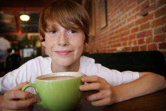Freckled boy with coffee in cafe