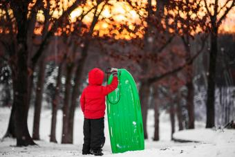 Boy standing in snow holding a sledge