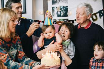 Family celebrating toddlers birthday with cake