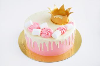 Cake with pink cream, white chocolate, decorated with marshmallow and gold crown