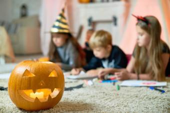 Halloween lantern with candle on shag carpet, kids drawing in background