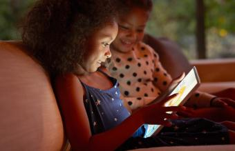 Two young girls playing on digital tablet