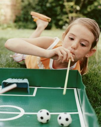 Girl blowing at soccer ball using straw