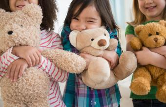 Girls hugging teddy bears