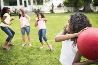 Girls playing dodgeball in backyard