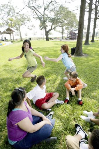 Children sitting in a circle and playing Duck, Duck, Goose