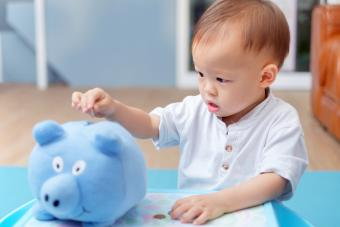 Toddler baby boy child putting coins into blue piggy bank