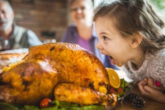 Girl pretending to bite cooked turkey