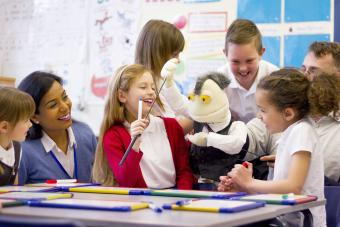 Kids having fun in class with pens and puppets