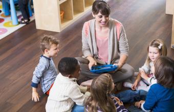 Teacher with preschoolers in class sitting on floor