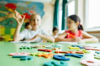 Kids with wooden toy plate alphabet in classroom