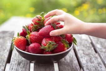 Girl's hand taking strawberry