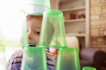 Smiling boy playing with plastic cups