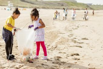 young girls collecting trash on beach