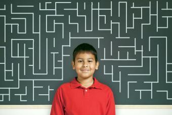 Child by chalkboard with maze