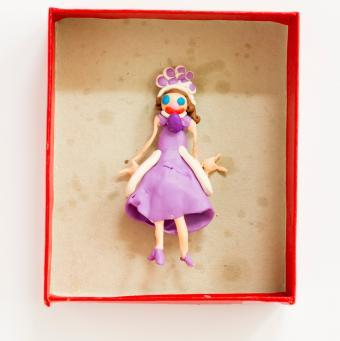 Clay doll sculpture in cardboard box