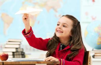 Girl looking at paper airplane