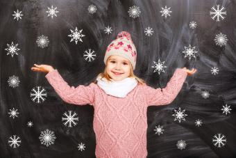 Girl stands on the background of of falling snowflakes