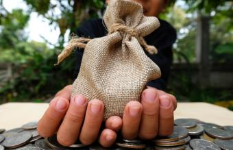 Hand Holding Sack On Coins