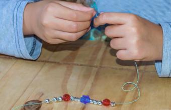 girl making a beaded bracelet