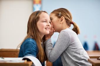 elementary school girl whispering in her friends ear in class