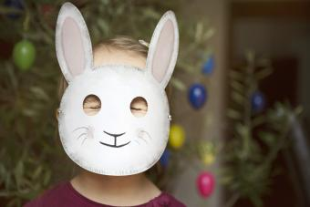 Child with eyes closed tight and wearing a rabbit mask