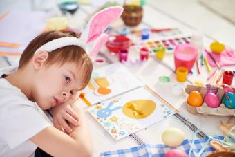 Little boy with rabbit ears lying on table with Easter eggs and handmade greeting cards