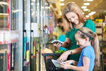 Mother and daughter using coupons at the grocery store
