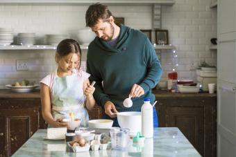 Father is assisting daughter baking in kitchen