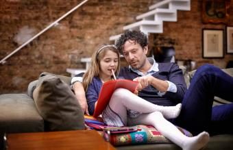 Father helping daughter with homework on couch