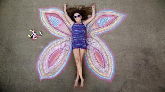 girl poses as the center of a butterfly drawn on the sidewalk with chalk