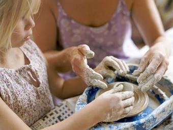Mother and daughter making a clay pot