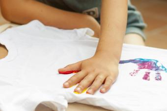 Boy hand printing T-shirt with paint