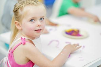 A young girl is sitting at a table finger painting